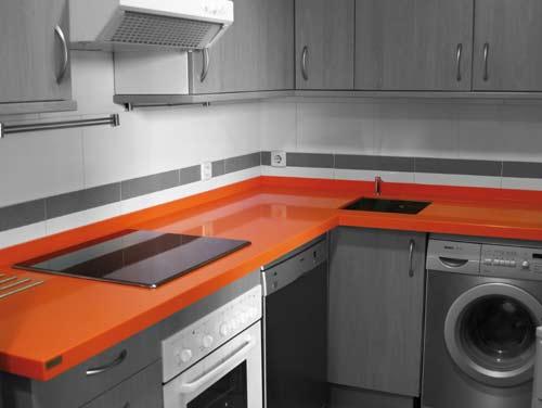 Foto de Cocina con Encimera naranja y muebles grises. Electrodomésticos en plata.