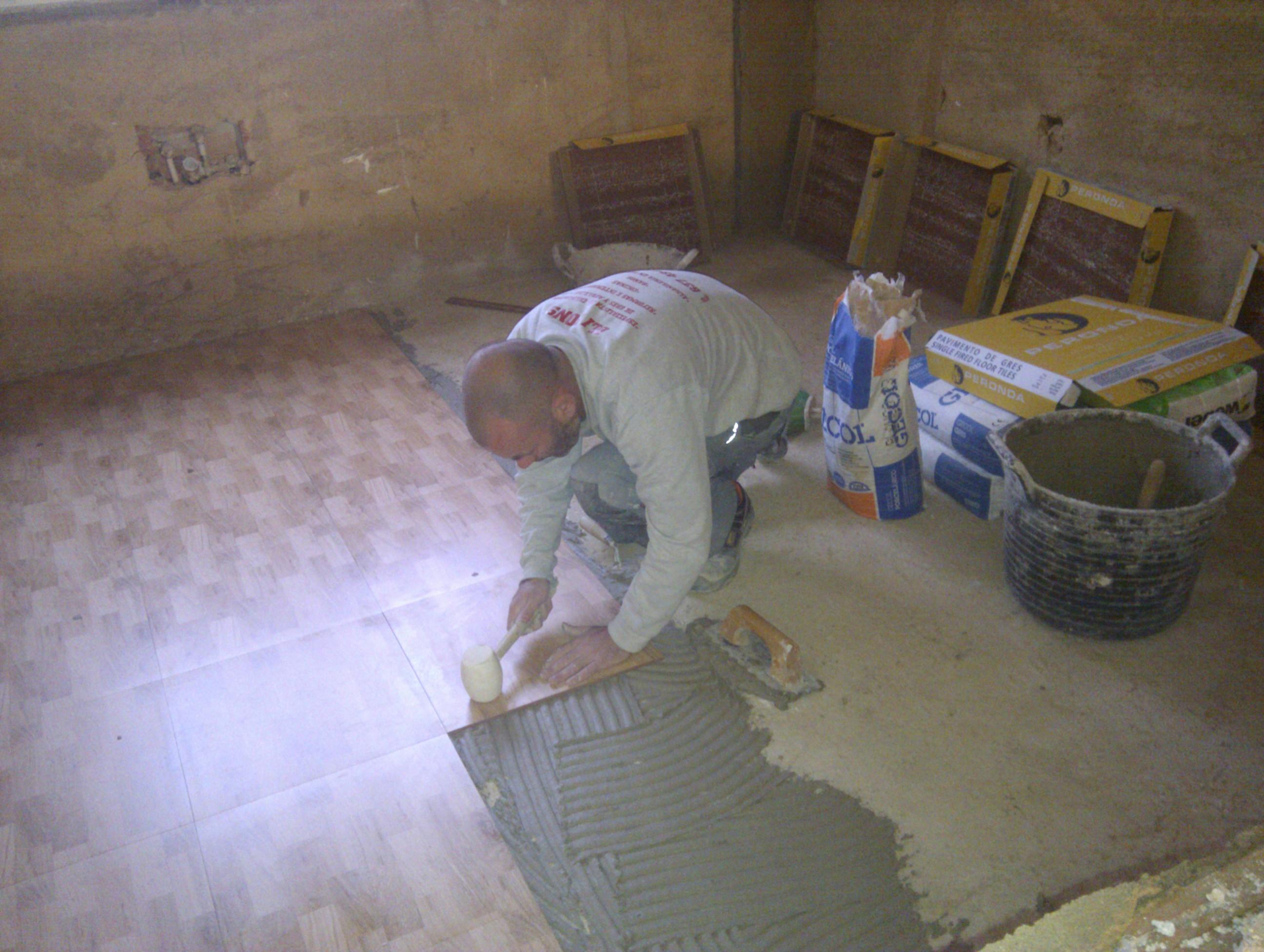 Colocando pavimento en Reforma realizada en Alcoy con la Técnica de Capa Fina, con adhesivo cemento-cola