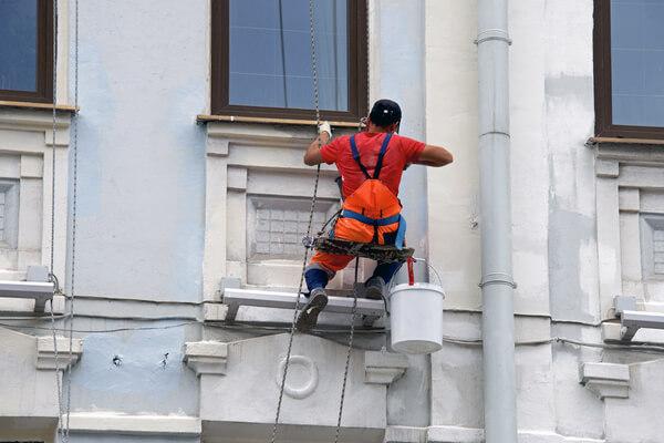 Trabajador pintando fachada de edificio azul.